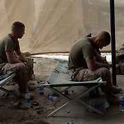 US Marines sit exhausted on their cots at Forward Operating Base Apache North in Garmsir District, Helmand Province, Afghanistan. Garmsir has been a haven for insurgents for the last several years. Earlier this year the Marines cleared the area after a period of heavy fighting and recently handed over control to British Forces.