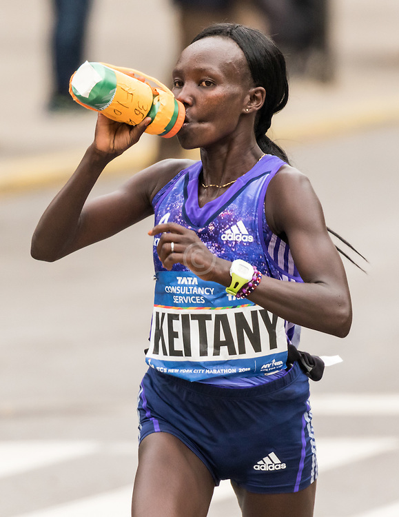 Mary Keitany, Kenya, take fluid bottle at mile 22 in Harlem on way to victory