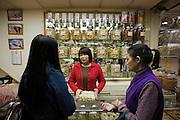 Women buying Chinese herbs and medicines in shop in Wing Lok Street, Sheung Wan, Hong Kong, China
