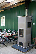 Wood burning stove, in a cafe. Llanerchaeron, Wales, UK. A wood burning stove used for heating and cooking in the cafe. Wood is a carbon neutral source of energy, as the amount of carbon dioxide that is released into the atmosphere when wood is burned is the same amount as that which is absorbed by the growing tree. A stove can spread or direct a fires heat much more efficiently than an open fire place.