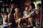 1989: 17+yr old Den Along (LHS) daughter of Along Sega, with her daughter Senorita, 1yr old (child in the arms of her cousin). They are indigenous Penan native people, living as semi-nomadic hunter gatherers. Long Tedan, Limbang district, Sarawak, Borneo 1989<br /> <br /> Tropical rainforest and one of the world's richest, oldest eco-systems, flora and fauna, under threat from development, logging and deforestation. Home to indigenous Dayak native tribal peoples, farming by slash and burn cultivation, fishing and hunting wild boar. Home to the Penan, traditional nomadic hunter-gatherers, of whom only one thousand survive, eating roots, and hunting wild animals with blowpipes. Animists, Christians, they still practice traditional medicine from herbs and plants. Native people have mounted protests and blockades against logging concessions, many have been arrested and imprisoned.