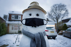 © Licensed to London News Pictures. 24/01/2021. Leatherhead, UK. A snowman built in the garden of a house near Leatherhead sports a face mask. A band of snow is crossed the south east this morning as temperatures remain just above freezing. Photo credit: Peter Macdiarmid/LNP