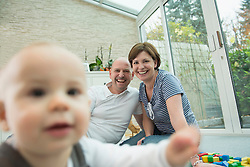 Parents and little son sitting on ground of living room
