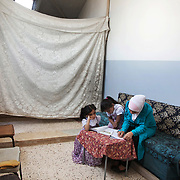 Douaa helps her two sisters with their home work. Douaa is from Sayeda Zeinab City in Syria. She was a geology student but had to leave Zeinab City with her family when the war came to their town. She lives with her father and siblings in a disused school in the Bekaa Valley.