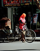 Street vendor with bicycle, Silk Route, Turpan, Xinjiang Province, China.