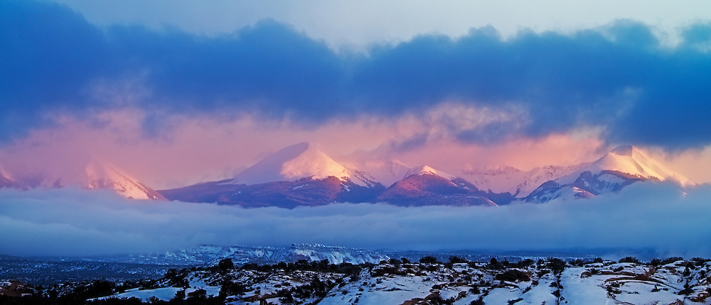 Mountains bathed in some late Alpenglow, shroueded by clouds.