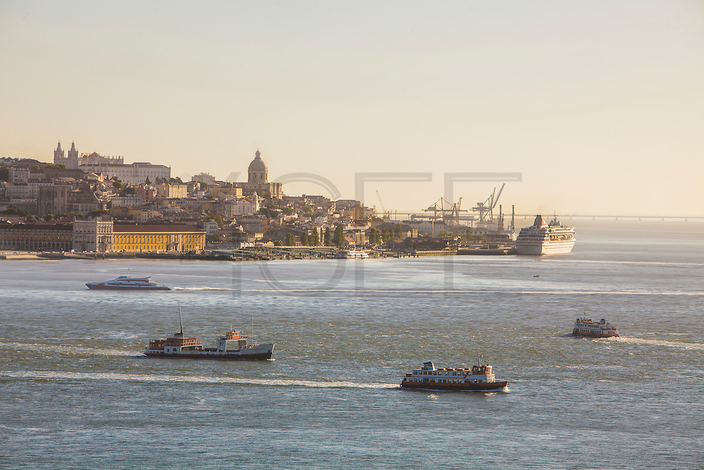 """Lisbon panorama seen from the south bank of Tagus river, in Almada. On the foreground tipical """"cacilheiro"""" ships cross the river. At the distance a cruise ship is docked at the cruise terminal."""