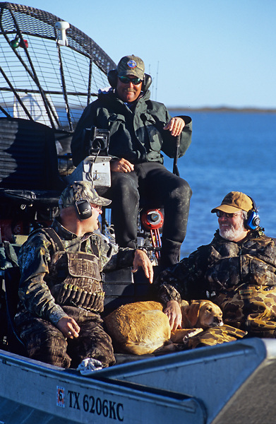 Stock photo of three men and their hunting dog in a fan boat returning from a trip