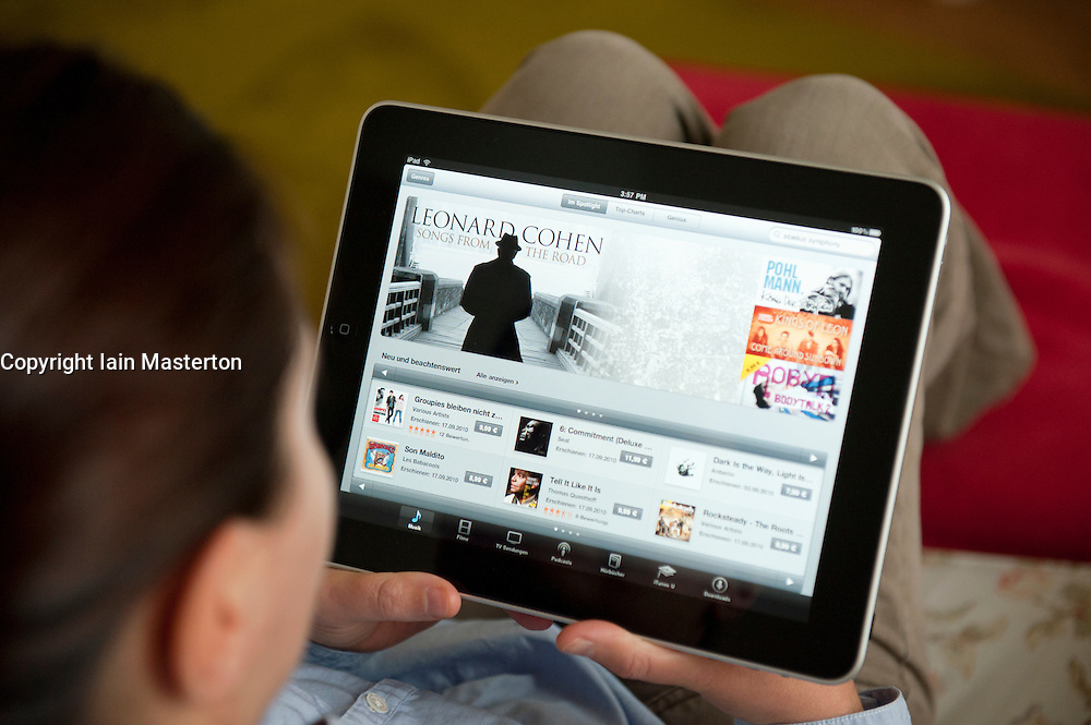 Woman using iPad tablet computer at home to browse iTunes digital music store