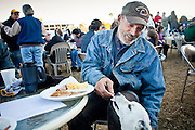 "Jan 10, 2010 - PHOENIX, AZ: RALPH, a homeless man in Phoenix, shares breakfast with his dog Buddy during breakfast at CrossRoads United Methodist Church in Phoenix, AZ. The church has been ordered by city zoning officials to stop serving breakfast to the homeless and indigent on Saturday mornings. The church started serving breakfast to the homeless in Jan. 2009 and shortly after that neighbors in the upscale area of Phoenix complained to city officials that the church was in violation of zoning ordinances. The city found the church was operating a ""charity kitchen"" and ordered them to stop serving the breakfast. Rev. Dottie Escobedo-Frank, the pastor of the church, has said the church will file an appeal in US District Court and continue serving the breakfast until the appeals process is exhausted. About 150 people attend the Saturday breakfast each week. Some walk to the church from the alleys they live in in the neighborhood, others are bused to the breakfast by the church, which sens a bus in 1.5 mile radius from the church.         Photo by Jack Kurtz"