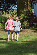 Two young friends girls walking through the grass with arm embracing back. Zawady Central Poland