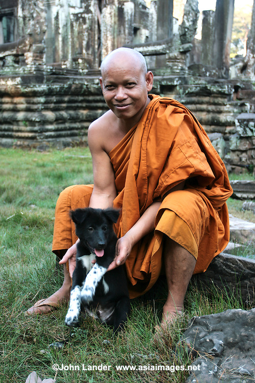 Friendly Buddhist monk playing with his dog on the grounds of Bayon, Angkor Thom.