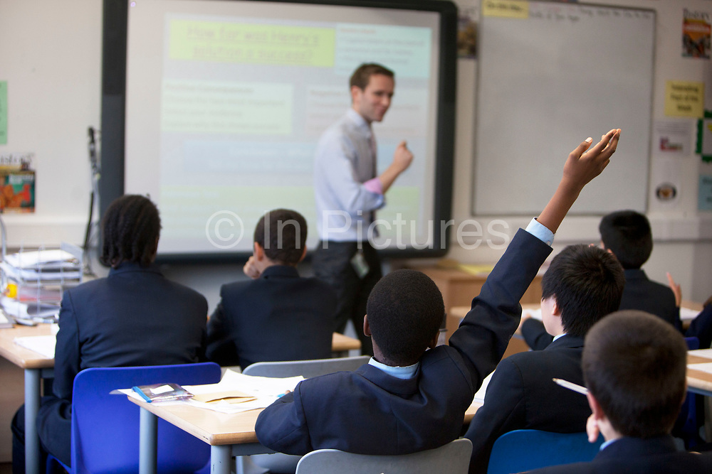 Teacher takes a history class as pupils raise their hands at Pimlico Academy, a modern secondary school in London, UK. Students education here is based on aspiration and is a huge success story following a large scale conversion.