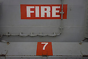 "Emergency fire muster station point on-board the Royal Navy's aircraft carrier HMS Illustrious. Illustrious is the second of three Invincible-class light aircraft carriers built for the Royal Navy in the late 1970s and early 1980s. She is the fifth warship and second aircraft carrier to bear the name Illustrious, and is affectionately known to her crew as ""Lusty"". She is the oldest ship in the Royal Navy's active fleet , expected  to be  withdrawn from service in 2014 (after 32 years' service)."