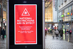 © Licensed to London News Pictures. 28/11/2020. Manchester, UK. People walk past a sign warning people that national restrictions are in effect. Manchester will enter Tier 3. Photo credit: Kerry Elsworth/LNP