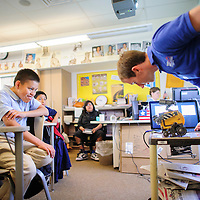 050714       Adron Gardner<br /> <br /> Josh LaFontaine, left, watches as Daniel Frank speaks to WALL-E the robot at Tsehootsooi Middle School in Fort Defiance Wednesday.