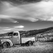 Black and white photo of a vintage truck in a rural field in Wyoming.