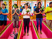 "24 JUNE 2017 - BANG KRUAI, NONTHABURI: People stand in their coffins during a ""resurrection"" or rebirthing ceremony at Wat Ta Kien (also spelled Wat Tahkian), a Buddhist temple in the suburbs of Bangkok. People go to the temple to participate in a ""Resurrection Ceremony."" Thai Buddhists believe that connecting people by strings around their heads, which are connected to a web of strings suspended from the ceiling, amplifies the power of the prayer. Groups of people meet and pray with the temple's Buddhist monks. Then they lie in coffins, the monks pull a pink sheet over them, symbolizing their ritualistic death. The sheet is then pulled back, and people sit up in the coffin, symbolizing their ritualist rebirth. The ceremony is supposed to expunge bad karma and bad luck from a person's life and also get people used to the idea of the inevitability of death. Most times, one person lays in one coffin, but there is family sized coffin that can accommodate up to six people. The temple has been doing the resurrection ceremonies for about nine years.     PHOTO BY JACK KURTZ"