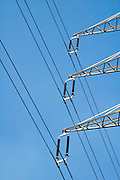 A high power electric line and pole with a blue sky background