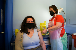 © Licensed to London News Pictures. 02/07/2021. London, UK. Vaccinator Shelley Salter administers the Pfizer Covid-19 vaccine to Natalie Glaz at a vaccination centre in Haringey, north London. According to Public Health England, a a total of 161,981 confirmed and probable cases of the Covid-19 Delta variant have now been identified in the UK. The government has said that it hopes all lockdown measures will be lifted from  19 July but has reportedly been discussing the possibility of reintroducing masks and social distancing during winter months. Photo credit: Dinendra Haria/LNP