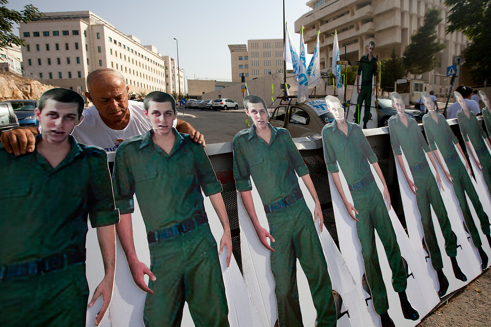 A protester places cardboard cut-outs depicting Israeli captured soldier Gilad Shalit in a row, during a demonstration calling for the release of Shalit, outside the Prime Minister's office in Jerusalem, on August 1, 2010.