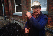Months after the fall of the Berlin wall and the collapse of the communist GDR state (German Democratic Republic), a brown coal delivery man stops to shovel his polluting fossil fuel into local cellars, on 15th June 1990, in Aue, Saxony. Aue is a mining town in the Ore Mountains known for its copper, titanium, and kaolinite. The town was a machine-building and cutlery manufacturing centre in the East German era with a population of roughly 18,000 inhabitants. It was the administrative seat of the former district of Aue-Schwarzenberg in Saxony and part of the Erzgebirgskreis since August 2008. (Photo by Richard Baker / In Pictures via Getty Images)