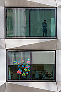 An employee and Post-it notes stuck to the window of a meeting room in an office on London Wall in the City of London - the capitals financial district, on 21st August 2018, in London, England.