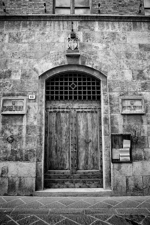 Black and white image of a dramatic entryway off of the streets of San Quirico d'Orcia, Italy.