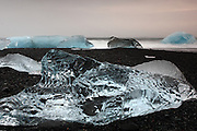 Icebergs from the Jökulsárlón glacial lake pour into the sea and wash up on the black volcanic sandy beach, in South-East Iceland. Images taken at dawn on two cloudy, foggy days in March.