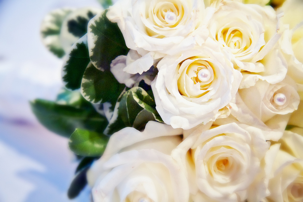 The bride's beautiful wedding bouquet. The flowers (roses) are adorned with pearls.