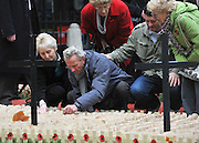 © Licensed to London News Pictures. 10/11/2011. London, UK. A family help a man look for a particular cross.  HRH The duke of Edinburgh opens the annual Field of Remembrance at Westminster Abbey today 10 November. . Photo credit : Stephen Simpson/LNP
