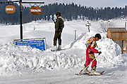 A young skier passes an Indian soldier protecting the ski resort of Gulmarg in Kashmir.  Gulmarg is famed for its gondola (3980m), the gondola which opened in 2005 is the worlds highest and has been drawing snowboarders and skiers from around the world. Gulmarg is only 10km from the line of control that seperates Pakistan Kashmir from Indian Kashmir which means its situated in a conflict zone. But improved relations between the two countries as well as a peace process within Kashmir have meant more skiers are now flocking to the area for what is said to be some of the best skiing in the world.