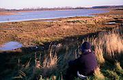 A3A7XC Woman in winter sitting Butley Creek Suffolk England