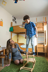Boy balancing on rocking horse while pregnant mother is watching, Munich, Germany