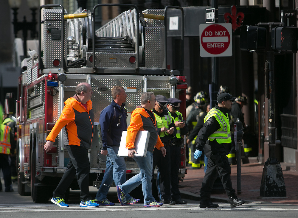 Boston, MA 04/15/2013.Officials escorted by a Boston Police officer carry computer hard drive systems down Exeter Street away from the Prudential Tower in Boston's Back Bay neighborhood after a bombing attack during the Boston Marathon on Monday..Alex Jones / www.alexjonesphoto.com