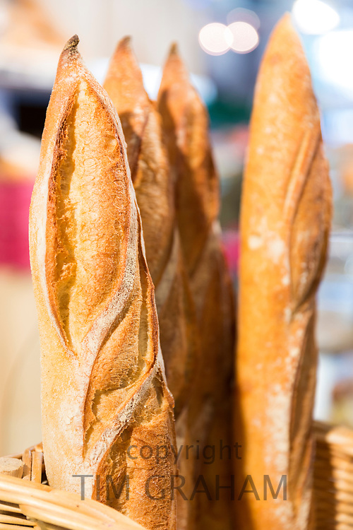 French baked baguette loaves of bread (traditional baguettes) on display for sale in food market on Ile de Re, France