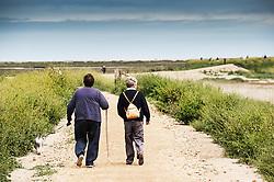 Friends walking along a track at Blakeney. Norfolk