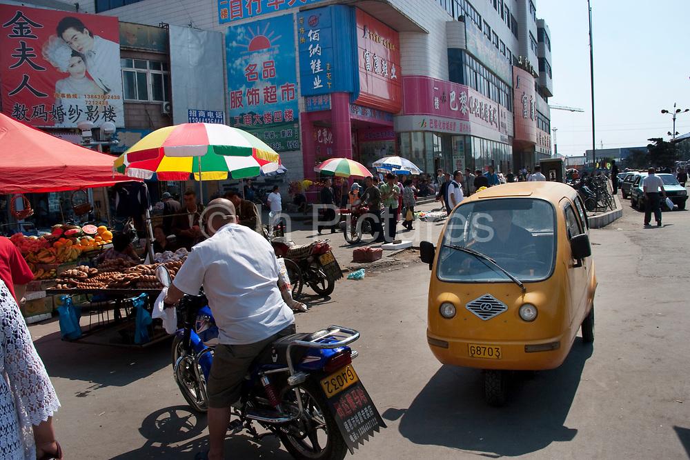 A strange looking yellow single seat car and street scene in De Hui city, Jilin Province. North Eastern China.