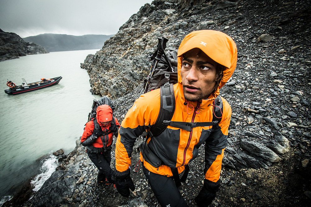 Two adventurers leaving an inflatable boat and starting a hike in Torres del Paine NP, Chile.