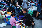 Refugees, Keleti station Budapest, Hungary. A group of Hungarian child volunteers help refugee children find clothes that fit them.