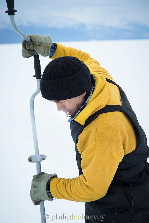 Fisherman drilling hole in the ice on Lake Baikal. Siberia, Russia