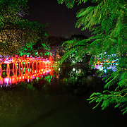 The Huc Bridge (Morning Sunlight Bridge) with trees at night. The red-painted, wooden bridge joins the northern shore of the lake with Jade Island and the Temple of the Jade Mountain (Ngoc Son Temple).