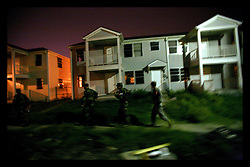 26 July 2006 - New Orleans - Louisiana. Law and Order. <br />2228 MP Company, Louisiana National Guard. Military Police patrol. 5th District. <br />With crime beginning to pick up as people return to the city following the destruction of Hurricane Katrina, 300 Louisiana National Guardsmen returned to New Orleans to supplement local police and provide increased cover and back up in parts of the city that remain derelict and thinly populated since the devastating floods. Following the sounds of gunshots, MP's move on foot patrol through the streets looking for the possible source. Criminals will sometimes fire shots to distract patrols in one area whilst they commit crimes somewhere else nearby.