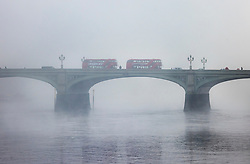 © Licensed to London News Pictures. 05/11/2020. London, UK. Red London buses cross a foggy River Thames on Westminster Bridge in central London on the first day of England's national lockdown. Photo credit: London News Pictures