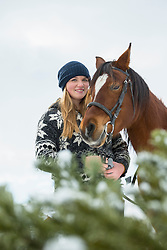 Portrait of a teenage girl with horse in farmland during winter, Bavaria, Germany