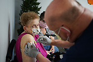 Mary Schlauch, left, is injected with her second dose of the Moderna vaccine by critical care registered nurse Timothy Brewer, right, as Lehigh Valley Health Network brought their mobile vaccination clinic to Majestic House on May 6, 2021, which offers low income housing to Seniors 55 years and over, in Tamaqua, Pennsylvania.