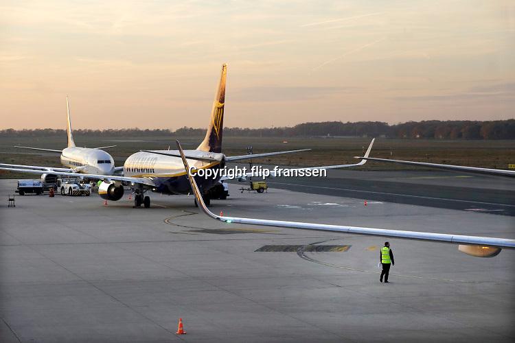 Duitsland, germany,deutschland, Weeze, 14-11-2018 Vlak over de grens van nederland ligt het regionaal vliegveld Niederrhein, Weeze, wat in tien jaar uitgegroeid is tot een belangrijke regionale luchthaven en als thuisbasis fungeert voor prijsvechter, chartermaatschappij Ryanair. In de regio bevindt zich ook vliegveld Dusseldorf. Een crew, bemanning gaat aan boord voor een vlucht naar Turijn, de piloot doet een check rondom het vliegtuig. . Naast passagiersvervoer wordt er veel luchtvracht vervoerd. Veel nederlanders uit oost gelderland, en noord limburg vliegen vanaf hier. Foto: Flip Franssen