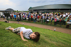 6 July 2017 -  Wimbledon Tennis (Day 4) - A young boy rolls down a hill near Court 1 as his family waits in line for Centre Court tickets - Photo: Charlotte Wilson / Offside.