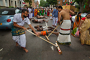 Hindu devotees carrying coconuts and covered with ash roll upon the London tarmac behind the chariot to participate in the annual Tamil chariot festival at the Murugan Temple in Highgate, London, England 17th July 2016. Thousands attend the colourful celebration as the temple's Goddess Amman (Tamil for Mother) is paraded on a beautifully decorated chariot pulled by the people through the streets around the temple, which brings to a close the four week Mahotsava festival.
