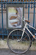 A poster of circles and spirals with a locked bicycle on railings outside Somerset House, Aldwych, central London.